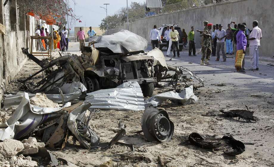 Somalis gather near one of the two car bombs used in the attack on the presidential compound in Mogadishu. The president was unharmed, but two government officials were killed. Photo: Farah Abdi Warsameh, Associated Press