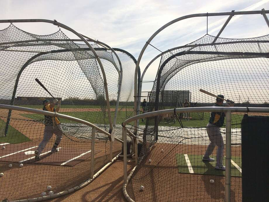 During their trips to Japan to play the Mariners in 2012 and the Red Sox in 2008, the A's picked up a new trend: side-to-side batting cages. They set up the double cages and pitching machines Friday at Papago Park for batting practice. Photo: Susan Slusser