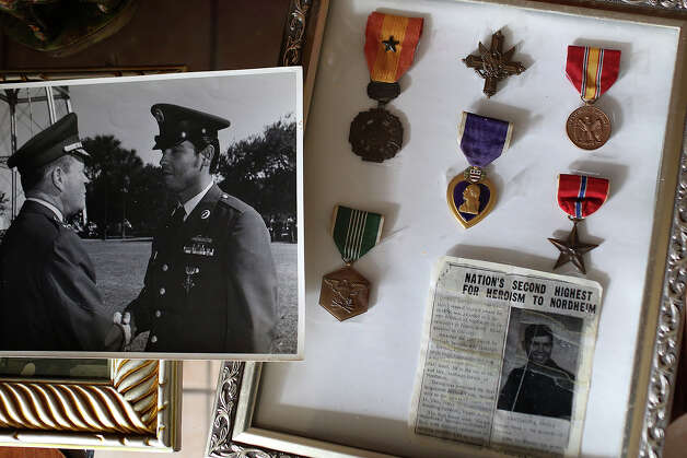 Medal of Honor recipient Santiago Erevia is seen in a photograph of a ceremony at Fort Sam Houston for his Distinguished Service Cross and his framed medals at his home in San Antonio on Tuesday, Feb. 18, 2014. Photo: Lisa Krantz / San Antonio Express-News