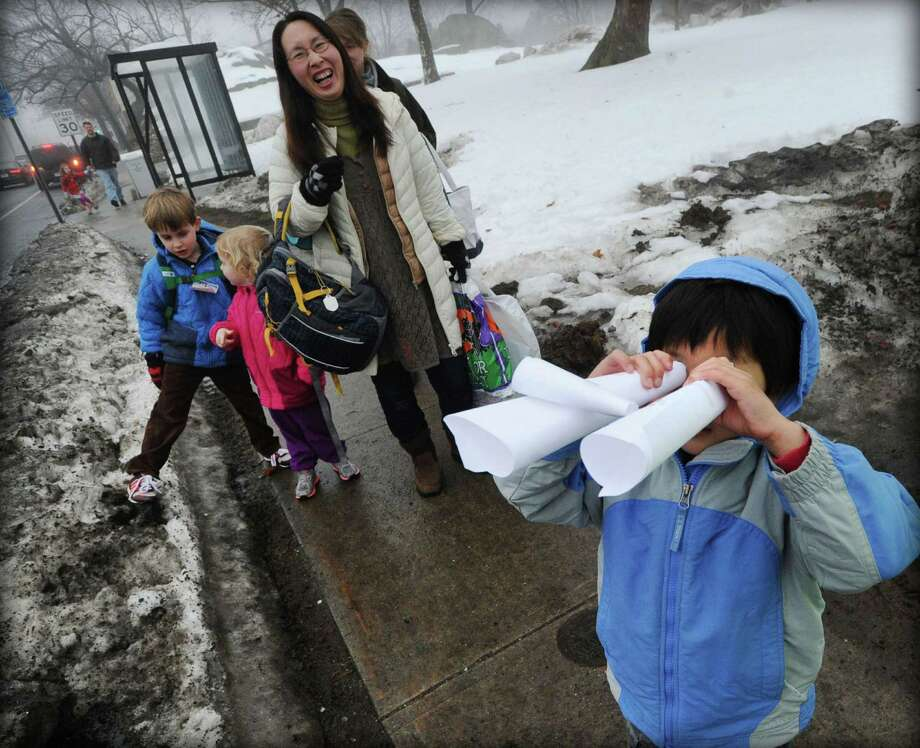 Cos Cob School kindergartener, Hiroki Morooka, 5, uses a pair of paper binoculars to check if East Putnam Avenue is clear of vehicles to help crossing guard, Carmine Gencarelli, 74, of Cos Cob, do his job at the crosswalk in front of the Cos Cob School in Greenwich, Conn., Friday afternoon, Feb. 21, 2014. Photo: Bob Luckey / Greenwich Time
