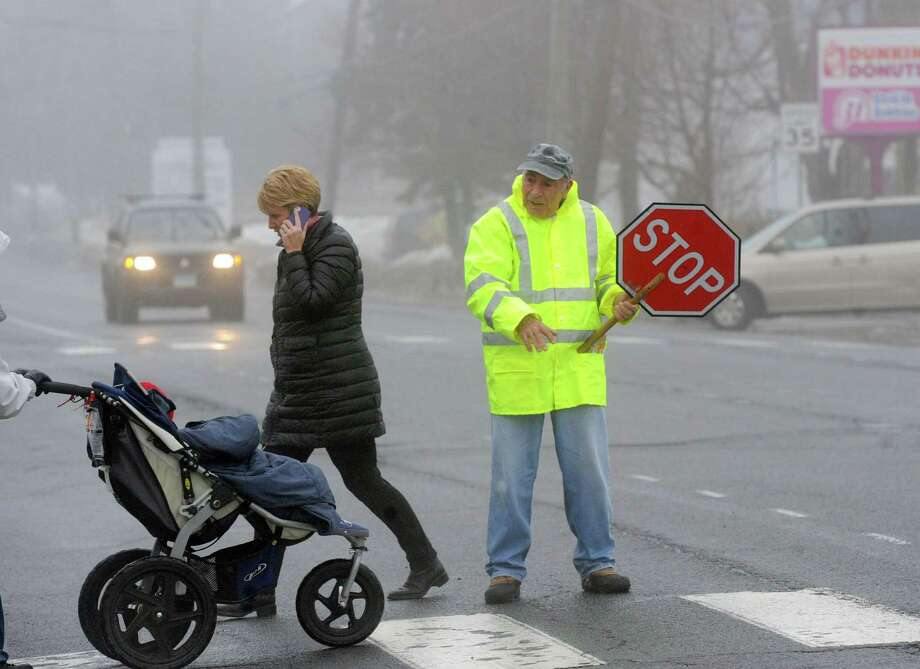 Crossing guard, Carmine Gencarelli, 74, of Cos Cob, on the job shepherding pedestrians across busy East Putnam Avenue directly in front of the Cos Cob School in Greenwich, Conn., Friday afternoon, Feb. 21, 2014.  Photo: Bob Luckey / Greenwich Time