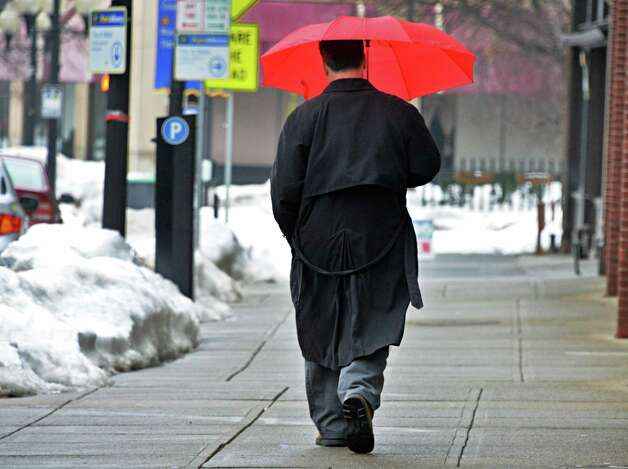 Shielded from Friday's rainy weather with by a red umbrella, Guy Bobersky of Colonie walks along Broadway Friday, Feb. 21, 2014, in Albany, NY.  (John Carl D'Annibale / Times Union) Photo: John Carl D'Annibale