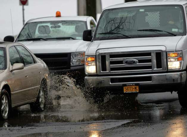 A driver runs in to a pot hole on Lake Avenue Friday morning Feb. 21, 2014 in Albany, N.Y.     (Skip Dickstein / Times Union) Photo: SKIP DICKSTEIN / 00025808A