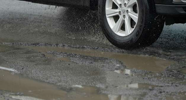A driver avoids a pot hole on Colvin Avenue Friday morning Feb. 21, 2014 in Albany, N.Y.     (Skip Dickstein / Times Union) Photo: SKIP DICKSTEIN / 00025808A