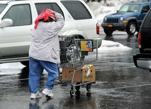 Raquel Catalano of Loudonville forgot her umbrella so she had to use a bandana to help keep her head dry Friday, Feb. 21, 2014, while leaving a  Price Chopper supermarket  in Loudonville, N.Y.   (Lori Van Buren / Times Union) Photo: Lori Van Buren