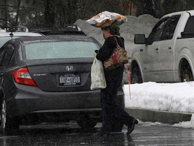 A woman uses a bag of pet food to help keep her head dry from a heavy rain while leaving a  Price Chopper supermarket Friday, Feb. 21, 2014, in Loudonville, N.Y.   (Lori Van Buren / Times Union) Photo: Lori Van Buren