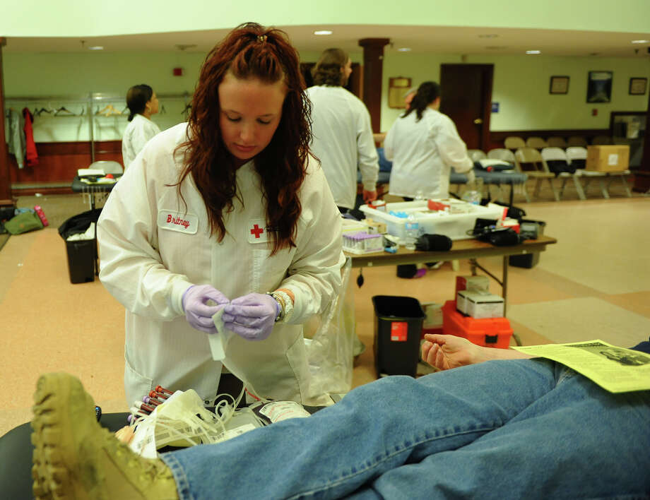 Phlebotomist Brittney Magee labels blood given bya donor, during a blood drive held by the American Red Cross at the Baldwin Senior Center in Stratford, Conn. on Friday February 21, 2014. The winter weather has resulted in an urgent need for blood donations according to the Red Cross. Visit www.redcrossblood.org/ct to find a blood drive in your area. Photo: Christian Abraham / Connecticut Post