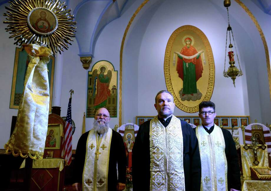 The Rev. Ivan Mazuryk, of Holy Protection of the Blessed Virgin Mary Ukrainian Catholic Church, center, stands with the Rev. Stephen Masliuk, left, of St Mary's Protection Ukrainian Orthodox Church, and the Rev. Oleksandr Dviniatin, of Holy Trinity Ukrainian Orthodox Church, Friday, Feb. 21, 2014 in the sanctuary of Holy Protection of the Blessed Virgin Mary in Bridgeport, Conn.  All three Ukrainian parishes in Bridgeport are holding a memorial service or Panachyda following the Divine Liturgy on Sunday to pray for those killed during the crisis in Ukraine. Photo: Autumn Driscoll / Connecticut Post