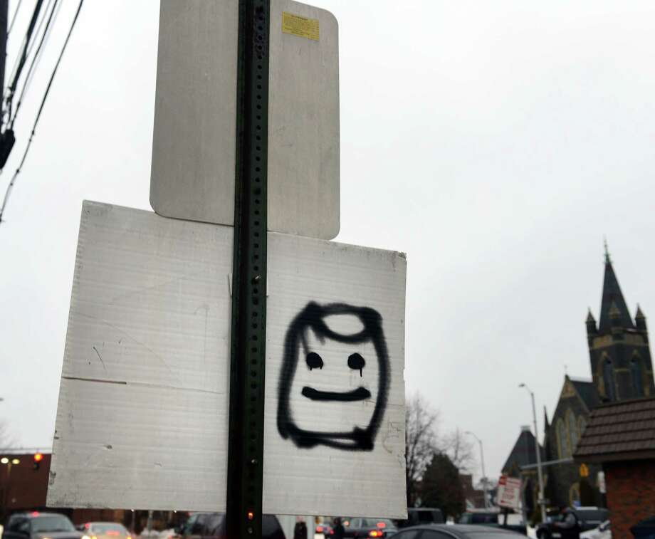 """Marshmallow Man"" Brian Riley, who has left his smiling graffiti tag on signs and walls in Bridgeport, like this one on John Street, was arrested Feb. 20, 2014, and charged with third-degree criminal mischief. Photo: Autumn Driscoll / Connecticut Post"