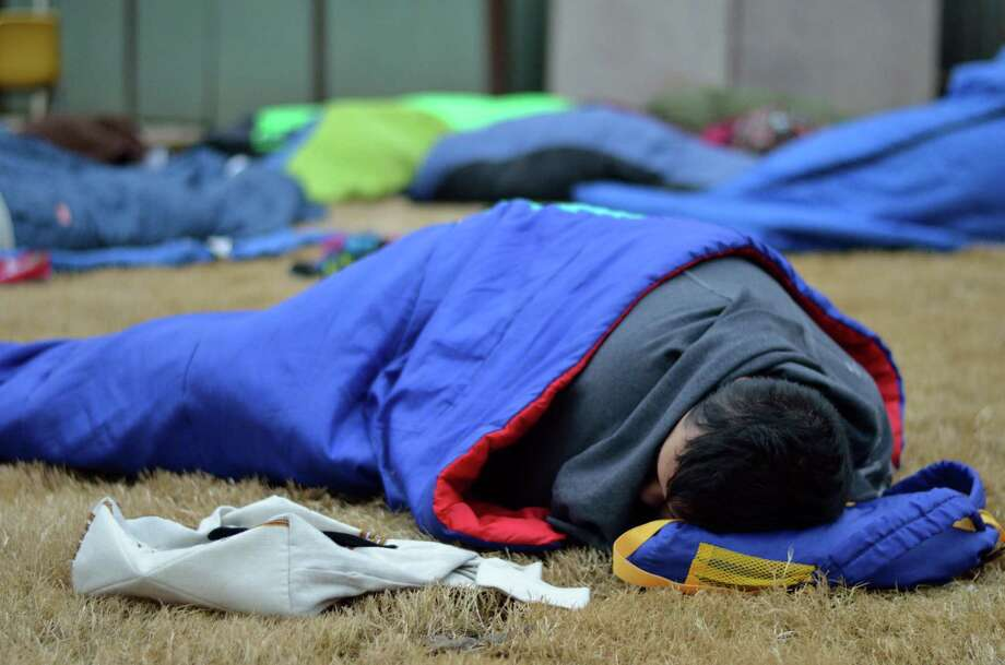 "A teen burrows into a sleeping bag to stay warm during a ""poverty simulation"" at Mission Waco. Photo: Monica Rhor"