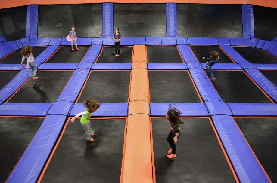 Children jump on one of the trampoline courts during the grand opening of Sky Zone Indoor Trampoline Park in Bethel, Conn. Thursday, Feb. 20, 2014.  Sky Zone contains several large trampoline courts including ones with a foam pit for learning tricks and basketball hoops for slam dunking.  The facility also offers SkyRobics fitness classes, 3D dodgeball tournaments and the SkyRiser bungee trampoline. Photo: Tyler Sizemore / The News-Times