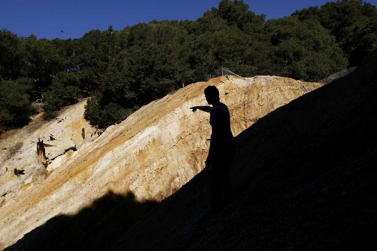 Laura Post checks out the abandoned sulfur mine which has been contaminating the creek by her home in Oakland, Calif., on Friday, February 21, 2014. The creek runs orange from runoff from a mine closed decades ago, and may finally be cleaned up.