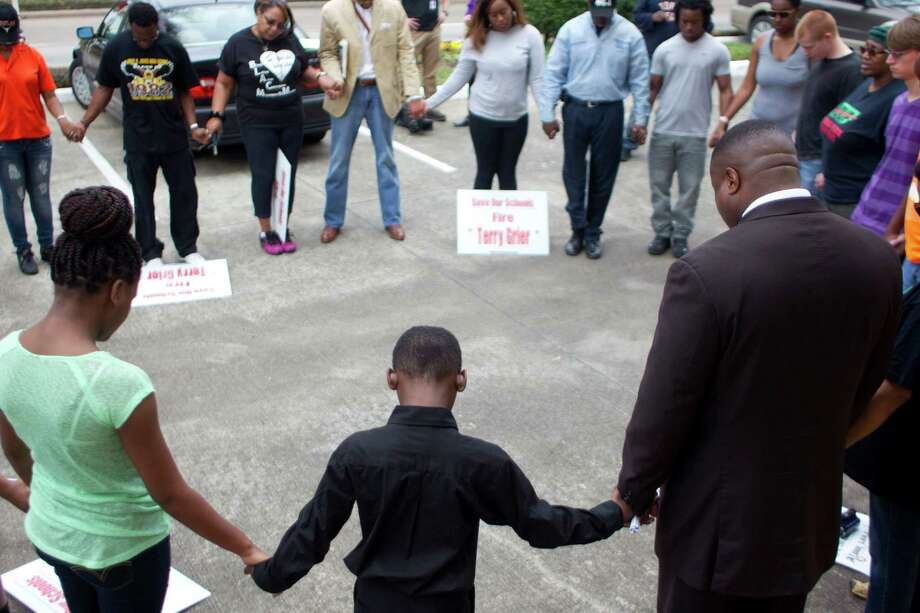 A group of about 25 people, including Stephen Church Manley Jr., 8, center, prays outside the Galleria neighborhood residence of HISD Superintendent Terry Grier on Sunday. They oppose the proposed closure of five HISD schools. Photo: Johnny Hanson, Staff / © 2014  Houston Chronicle