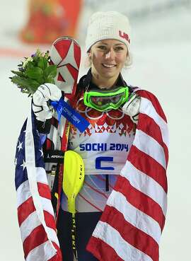 Gold medallist US skier Mikaela Shiffrin poses with the stars and stripes on the podium during the Women's Alpine Skiing Slalom Flower Ceremony at the Rosa Khutor Alpine Center during the Sochi Winter Olympics on February 21, 2014.     AFP PHOTO / ALEXANDER KLEINALEXANDER KLEIN/AFP/Getty Images
