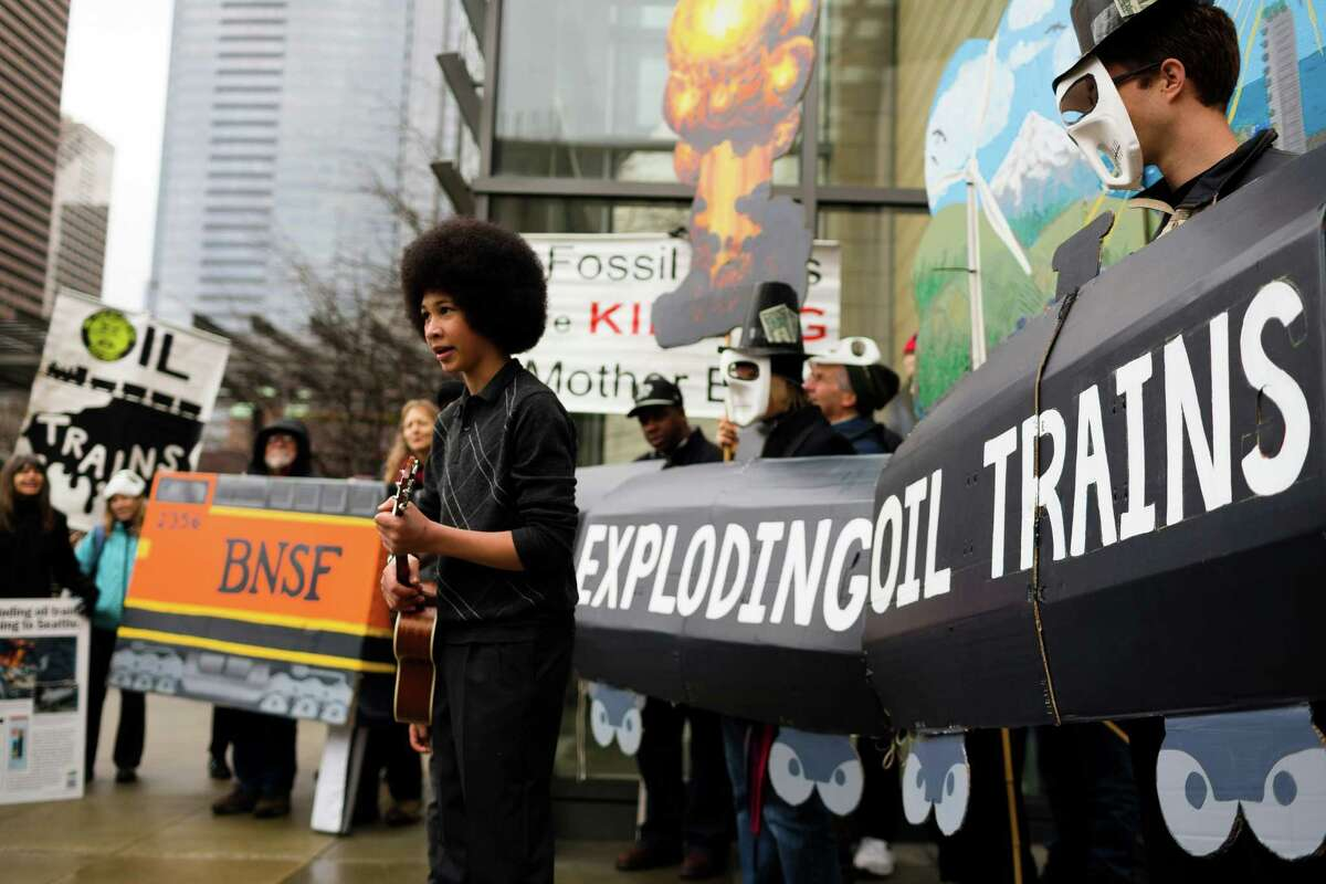 Aji Piper, center left, and brother Adonis behind him, perform a song during a rally for the need of a statewide moratorium on potentially dangerous oil-by-rail projects Friday, Feb. 21, 2014, at City Hall in Seattle. Oil trains have exploded in different regions in the U.S., causing death and property damages.