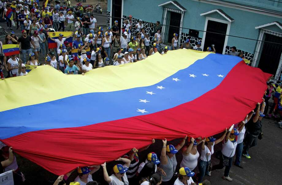 Mothers of Venezuelan anti-government students hold a national flag during a protest against President Nicolas Maduro in San Cristobal. Photo: LUIS ROBAYO, Stringer / AFP ImageForum