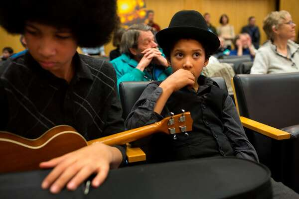 Aji Piper, left, and brother Adonis Piper, right, pack up after performing a song for the Seattle City Council following a rally for the need of a statewide moratorium on potentially dangerous oil-by-rail projects Friday, Feb. 21, 2014, at City Hall in Seattle. Oil trains have exploded in different regions in the U.S., causing death and property damages. (Jordan Stead, seattlepi.com)