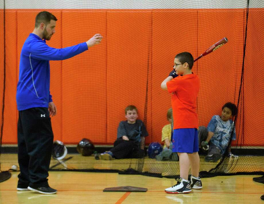 Jeremy Young, 9, gets a tip from Steve Buckett as he practices hitting the ball during the last day of EST Baseball's week-long Winter Hitting, Speed and Agility Clinic at Stamford High School on Friday, February 21, 2014. Photo: Lindsay Perry / Stamford Advocate