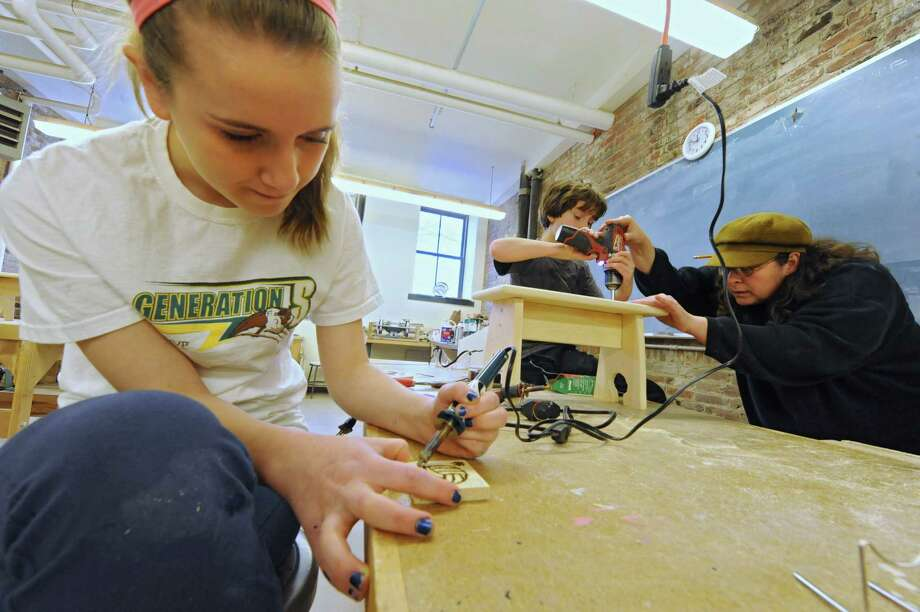 Athena Conzone, left, 13, of East Greenbush uses a wood burning tool as Eland Colon, 10, of Duanesburg gets help from woodworking instructor Melissa Colins while making step stool Friday, Feb. 21, 2014, at The Arts Center in Troy, N.Y. Winter break camps at The Arts Center are in session for elementary, middle and high school students.  (Lori Van Buren / Times Union) Photo: Lori Van Buren / 00025846A