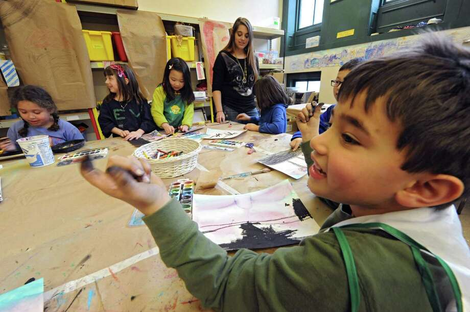 Instructor Jennifer Tayne, center, teaches a mixed media class called Winter At The Beach as Kevin Rosas, 6, of Saratoga Springs shows his messy hands to a friend Friday, Feb. 21, 2014, at The Arts Center in Troy, N.Y. Winter break camps at The Arts Center are in session for elementary, middle and high school students.  (Lori Van Buren / Times Union) Photo: Lori Van Buren / 00025846A