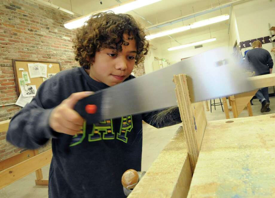 Corey da Silva, 10, of Poestenkill uses a saw to cut a piece of wood while taking a woodworking class at The Arts Center on Friday, Feb. 21, 2014, in Troy, N.Y. Winter break camps at The Arts Center are in session for elementary, middle and high school students.  (Lori Van Buren / Times Union) Photo: Lori Van Buren / 00025846A