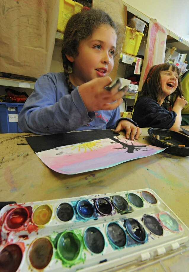 Sofi Collins, 6, of Latham, left, works on a painting as Ellie Schabses, 6, of West Sand Lake laughs at another student during a mixed media class called Winter At The Beach Friday, Feb. 21, 2014, at The Arts Center in Troy, N.Y. Winter break camps at The Arts Center are in session for elementary, middle and high school students.  (Lori Van Buren / Times Union) Photo: Lori Van Buren / 00025846A