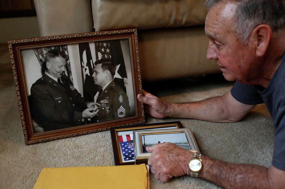 Medal of Honor recipient Jose Rodela finds a photograph of himself receiving the Distinguished Service Cross at Fort Sam Houston in 1969, at his home in San Antonio on Tuesday, Feb. 18, 2014. Photo: Lisa Krantz, San Antonio Express-News / San Antonio Express-News