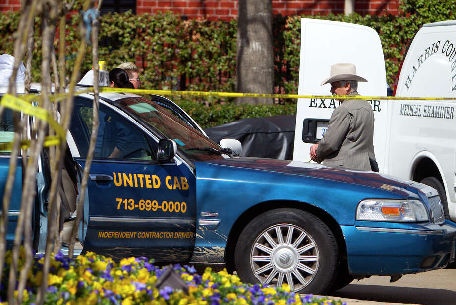 The body of a taxi driver is removed Friday after he was found slumped behind the wheel of his cab outside an apartment complex near West University Place. Photo: Cody Duty, Staff / © 2014 Houston Chronicle