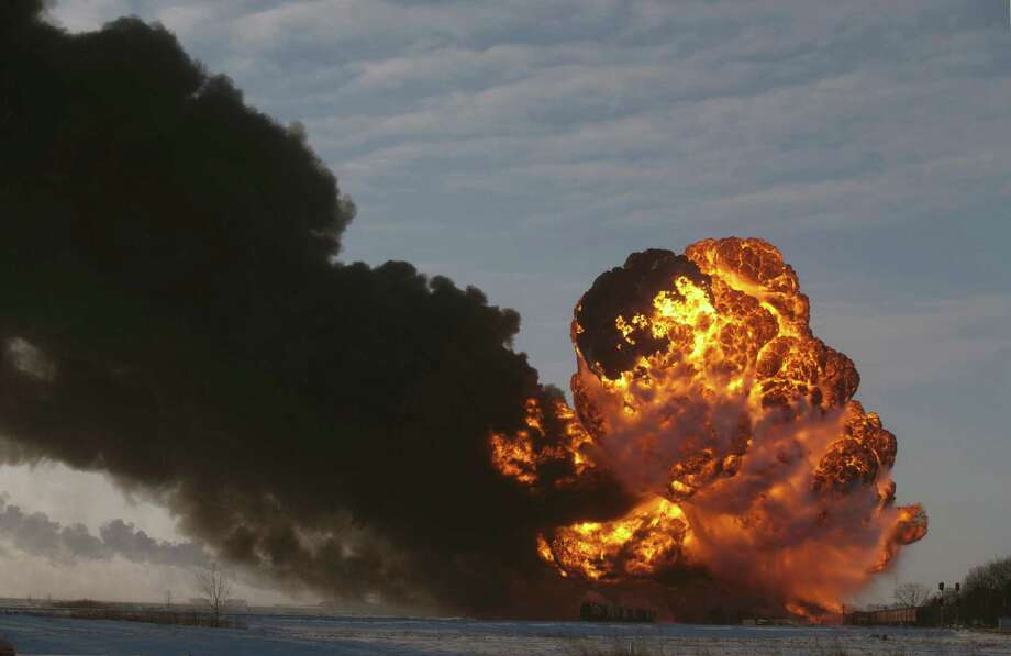 FILE - In this Dec. 30, 2013 file photo, a fireball goes up at the site of an oil train derailment in Casselton, N.D.  Railroads that haul volatile crude shipments have reached an agreement with U.S. transportation officials to adopt wide-ranging voluntary safety measures after a string of explosive and deadly accidents. A copy of the agreement between the U.S. Transportation Department and the Association of American Railroads obtained Friday, Feb. 21, 2014 by The Associated Press calls for railroads to slow down oil trains through major cities, increase track inspections and bolster emergency response planning along routes that see trains that can haul up to three million gallons of oil each. (AP Photo/Bruce Crummy, File) Photo: Bruce Crummy, FRE / FR6524 AP
