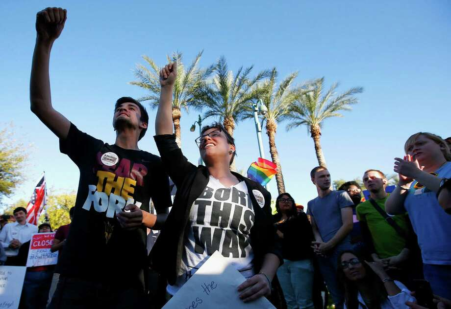 Anthony Musa, left, and Brianna Pantillione join nearly 250 gay rights supporters protesting a bill that would allow business owner to refuse service to gays. Photo: Ross D. Franklin, STF / AP