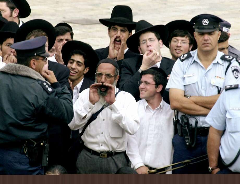 Ultra-Orthodox Jews heckle women praying at the Western Wall in Jerusalem's Old City Sunday June 4, 2000, as Police Commander Yair Yitzhaki, right, looks on.  Dozens of Jewish women, some draped in prayer shawls, prayed out loud at the Western Wall Sunday, defying a bill that would sentence them to seven years in prison.   (AP Photo/Elizabeth Dalziel) Photo: AP