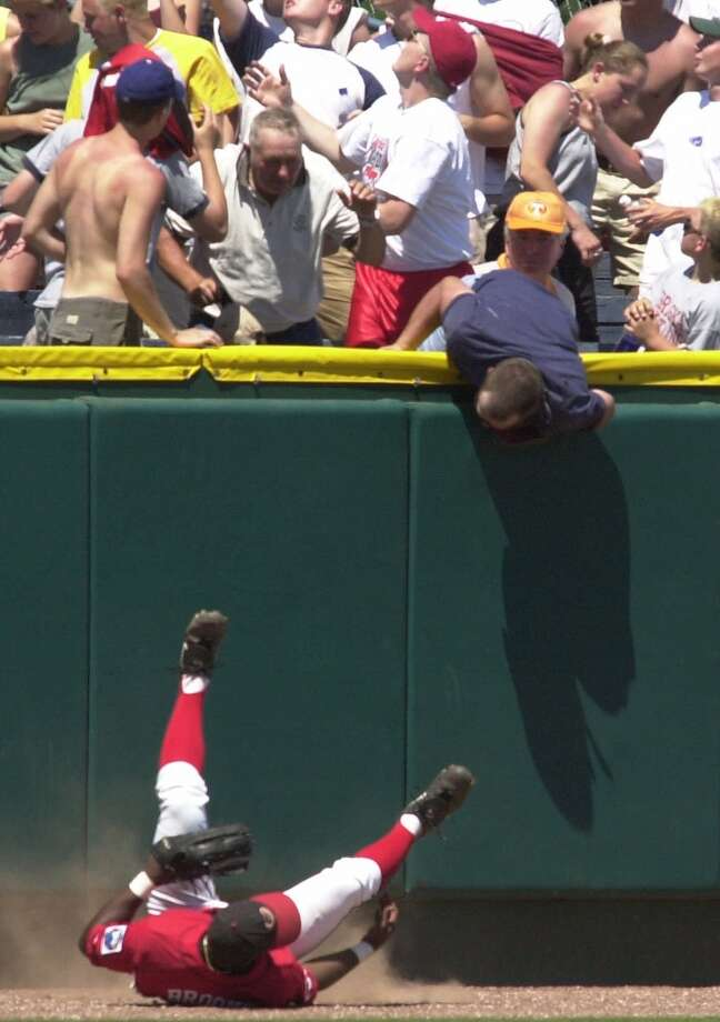 Georgia's Doc Brooks, chasing after a home run ball by USC's Bill Peavey, falls on his back and is heckled by a fan after colliding with the wall in the seventh inning of the  College World Series bracket two game against Georgia held in Omaha, Neb., Saturday June 9, 2001. USC won the game 11-5.   (AP Photo/Dennis Grundman)  HOUCHRON CAPTION  (06/10/2001):  Georgia's Doc Brooks falls on his back and is heckled by a fan after unsuccessfully trying to chase down a home run hit by USC's Bill Peavey during the Trojans' 11-5 win Saturday. Photo: AP