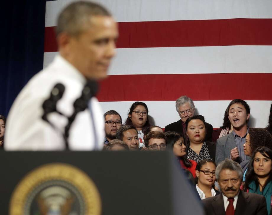 In this Nov. 25, 2013, photo, President Barack Obama, left, stops his speech and turns around in response to an unidentified man, right, who heckled him about anti-deportation policies, at the Betty Ann Ong Chinese Recreation Center in San Francisco. Obama stopped his speech about immigration reform to let this man, who was located directly behind Obama, speak and would respond to his questions. Advocates are frustrated with the failure of House Republicans to tackle immigration. Increasingly, they're focus is on President Barack Obama. The outside groups are demanding that Obama use his powers as chief executive to stop deportations or provide some relief to many of the 11 million immigrants living here illegally.  (AP Photo/Pablo Martinez Monsivais, File) Photo: Associated Press