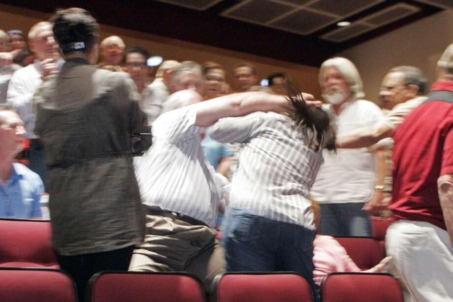 An unidentified man punches Kay Mehta  after a Senate candidate forum for Angle and Reid at Faith Lutheran High School Thursday, Sept. 23, 2010 in Las Vegas.   The fight came after an impassioned event during which the crowd both heckled and cheered Republican Sharron Angle and Democrat Harry Reid. (AP Photo/Las Vegas Sun, Sam Morris) Photo: AP