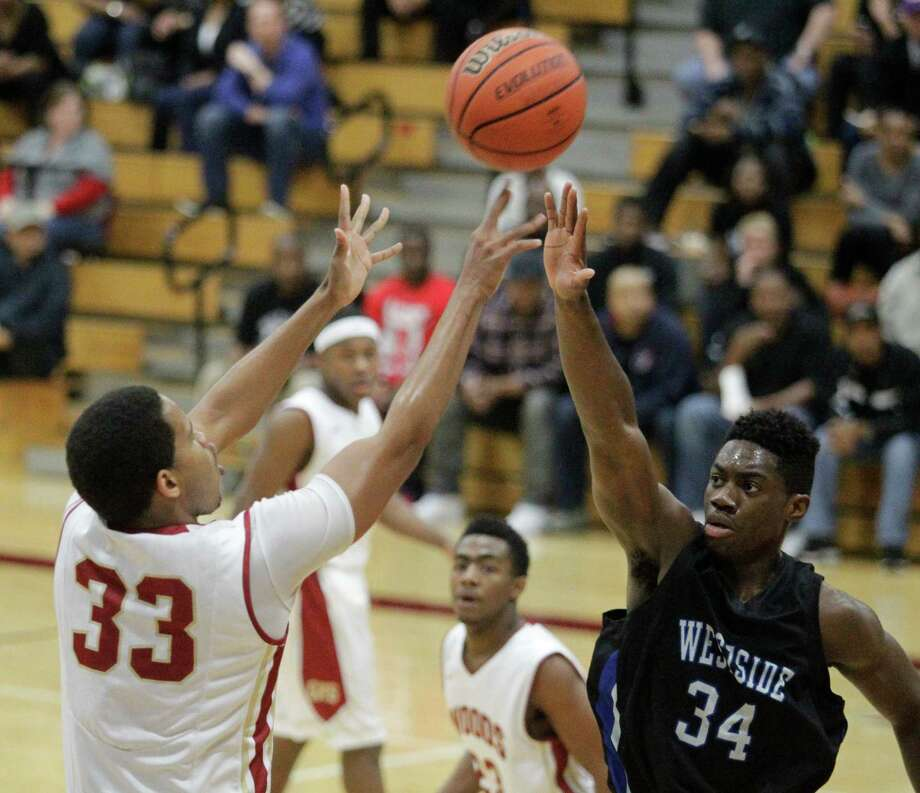 Cypress Woods forward Kellen Johnson (33) shoots as Westside forward Daniel Utomi (34) defends during the boys 5A area finals playoff basketball game at Cinco Ranch High School on Friday, Feb. 21, 2014, in Katy. Photo: J. Patric Schneider, For The Chronicle / © 2014 Houston Chronicle