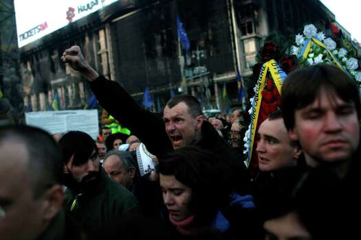"""A man shouts """"Glory to the Ukraine"""" during a funeral procession for anti-government protesters killed in clashes with the police at Independence Square in Kiev, Ukraine. The social uprisings and protests, both in Ukraine and Venezuela, have had a helping hand from Texas, as a new walkie-talkie app developed in Austin has been aiding protesters to communicate. Photo: Marko Drobnjakovic / AP"""