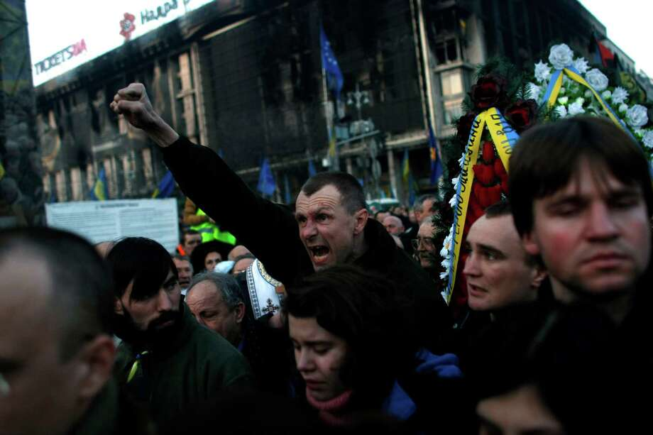 "A man shouts ""Glory to the Ukraine"" during a funeral procession for anti-government protesters killed in clashes with the police at Independence Square in Kiev, Ukraine. The social uprisings and protests, both in Ukraine and Venezuela, have had a helping hand from Texas, as a new walkie-talkie app developed in Austin has been aiding protesters to communicate. Photo: Marko Drobnjakovic / AP"