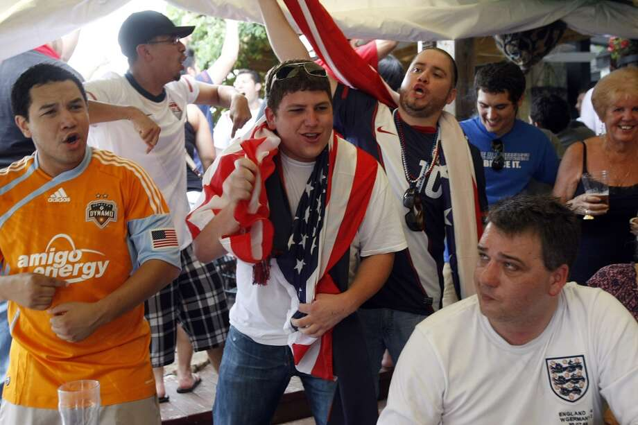 "Robert Ford (right) who is originally from London, England but now lives here in Houston, is heckled by U.S. soccer fans, (L to R) Malik Smith, Jason McClelland and Eric Ramirez  as hundreds of U.S. and England fans gathered at Richmond Arms Pub to watch the U.S. and England played to a 1-1 tie in the World Cup Friday, June 11, 2010, in Houston.  When asked how important the game was for England, Ford said. ""It doesn't compare to my first born, but perhaps my second. I may be leaving the country this afternoon if we lose."" ( Johnny Hanson / Chronicle ) Photo: Houston Chronicle"
