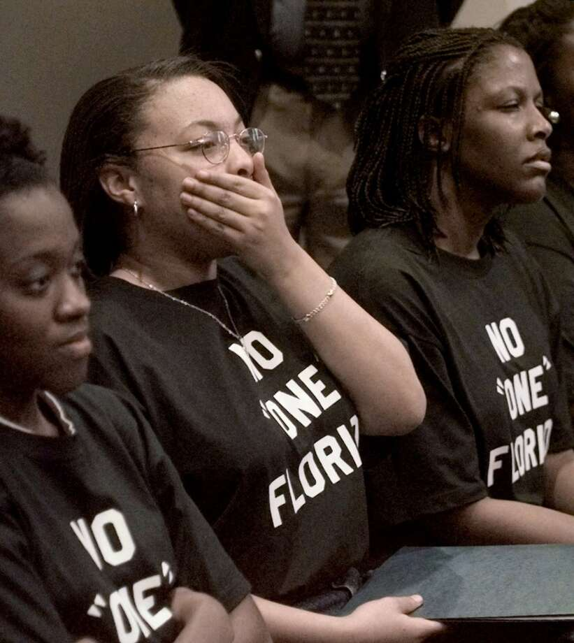Florida A&M University student Fredricka Irvine of Tallahassee, center, puts her hand to her mouth in disbelief as the crowd turned to heckling Lt. Gov. Frank Brogan during his speech at a 'One Florida' hearing Thursday, Feb. 10, 2000, in Tallahassee, Fla. From the left are FAMU students: Katrece Freeman of Miami, Irvine, and Nneka Sims of Lakeland.(AP Photo/Mark Foley)  HOUCHRON CAPTION (02/11/2000):  Florida A&M University student Fredricka Irvine, center, reacts to a speech at a One Florida hearing Thursday. Photo: AP