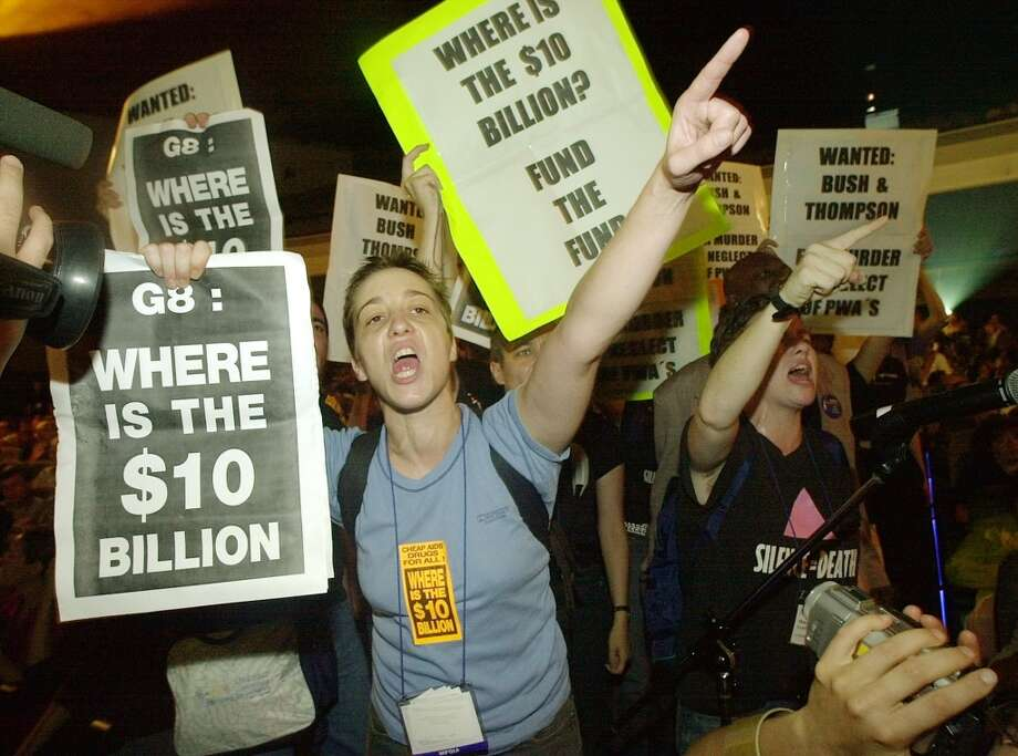 Members of the Act Up AIDS activist group heckle U.S. Secretary of Health and Human Services Tommy Thompson, during his address to delegates at the International AIDS conference in Barcelona, Spain, Tuesday July 9, 2002. The group was demanding more active US government support in the fight against AIDS. (AP Photo/Denis Doyle) Photo: AP