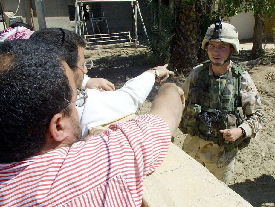Iraqis heckle a US soldier standing guard inside the troops' compound in Falluja, 50km east of Baghdad, 01 May 2003. Seven US soldiers were wounded when two unidentified men lobbed two grenades over the wall of their offices overnight, a US officer said. Two Humvee vehicles were damaged in the attack on the US troops' offices, set up in what used to be the local headquarters of the former ruling Baath Party in an area of central Fallujah where 16 people were shot dead by US troops this week.       AFP PHOTO/Rabih MOGHRABI.  HOUCHRON CAPTION  (05/02/2003):  Iraqis heckle a U.S. soldier as he guards a compound in Falluja, Iraq. The 82nd Airborne Division is handing over control of Falluja to the Armored Cavalry after a series of clashes there. Photo: AFP