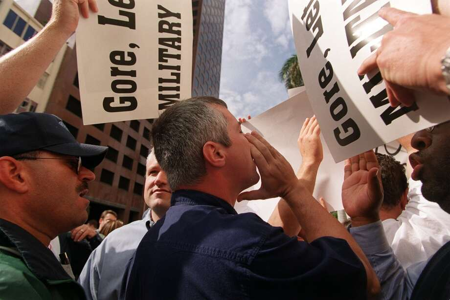 An unidentified Democratic protestor, center, is surrounded by Republican demonstarors as he shouts anti-Republican chants during Senator Bob Dole's speech in front of the Broward County Courthouse in downtown Fort Lauderdale Friday, November 24, 2000. The Broward County Canvassing Board continues its recount of ballots from the still undecided presidential election upstairs. (AP Photo/ Lynsey Addario)  HOUCHRON CAPTION (11/25/2000):  An unidentified Democrat, center, heckles former Sen. Bob Dole as he speaks Friday in front of the Broward County, Fla., Courthouse, where votes are still being recounted. The man is surrounded by Republicans in town to protest the recount. Photo: AP