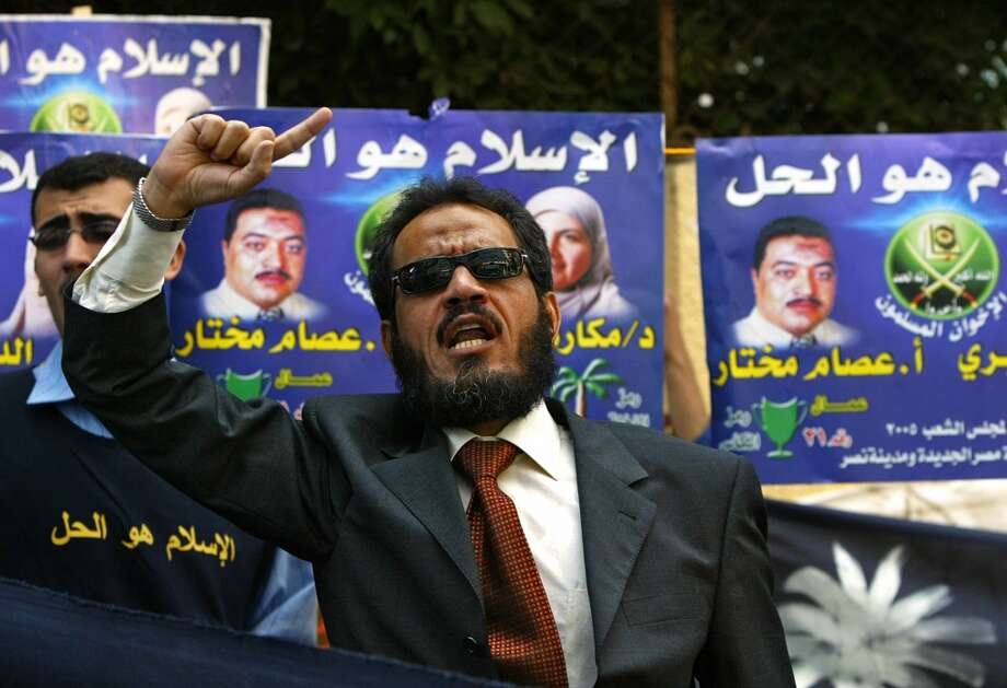 An Egyptian man heckles for candidates close to a polling station in Cairo during the parliamentary elections where eleven million Egyptians are expected to participate 09 November 2005. Thousands of polling stations opened for the first round of the initial phase in legislative elections that will last a month and are expected to see opposition parties make a small dent in the ruling party's dominance. AFP PHOTO/CRIS BOURONCLE  (Photo credit should read CRIS BOURONCLE/AFP/Getty Images) Photo: AFP/Getty Images
