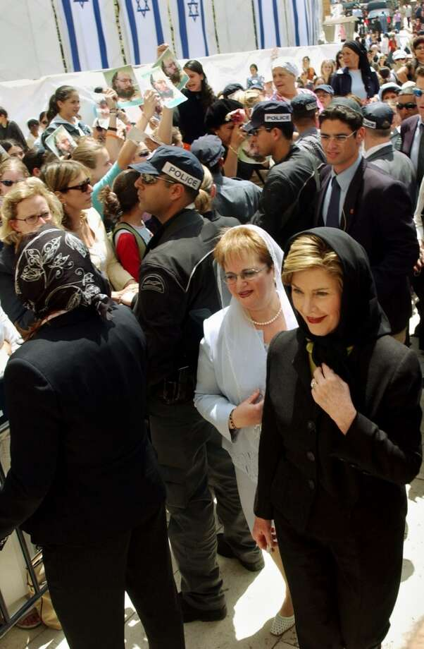 U.S. first lady Laura Bush and Gila Katsav, the wife of Israeli President Moshe Katsav, walk past demonstrators demanding the release of convicted Israeli spy Jonathan Pollard as they arrive at the Western Wall in Jerusalem's Old City Sunday May 22, 2005.  Anti-U.S. protesters later heckled Laura Bush at the Al Aqsa Mosque compound, during a Mideast tour meant to defuse growing  anti-American sentiment in the region.(AP Photo/Ariel Jerosolimski) ** ISRAEL OUT **.  HOUCHRON CAPTION (05/23/2005) SECNEWS COLORFRONT:  HELD BACK: First lady Laura Bush, right, and Gila Katsav, the wife of Israeli President Moshe Katsav, walk past police facing demonstrators in Jerusalem Sunday. Photo: AP