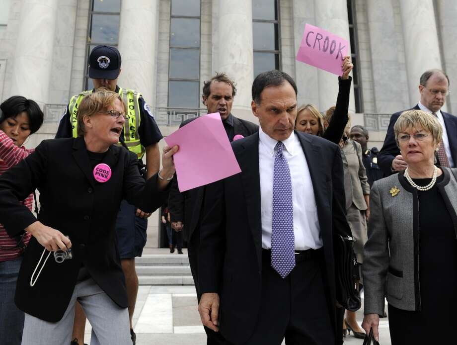 FILE - In this Oct. 6, 2008 file photo, Lehman Brothers Holdings Inc. Chief Executive Richard S. Fuld Jr., front center, is heckled by protesters as he leaves Capitol Hill in Washington after testify before the House Oversight and Government Reform Committee on the collapse of Lehman Brothers. A report by U.S. bankruptcy-court examiner faults Lehman Brothers  executives and auditor Ernst & Young for serious lapses that led to the largest bankruptcy in U.S. history. Will former CEO Richard Fuld be held accountable?(AP Photo/Susan Walsh, file) Photo: AP