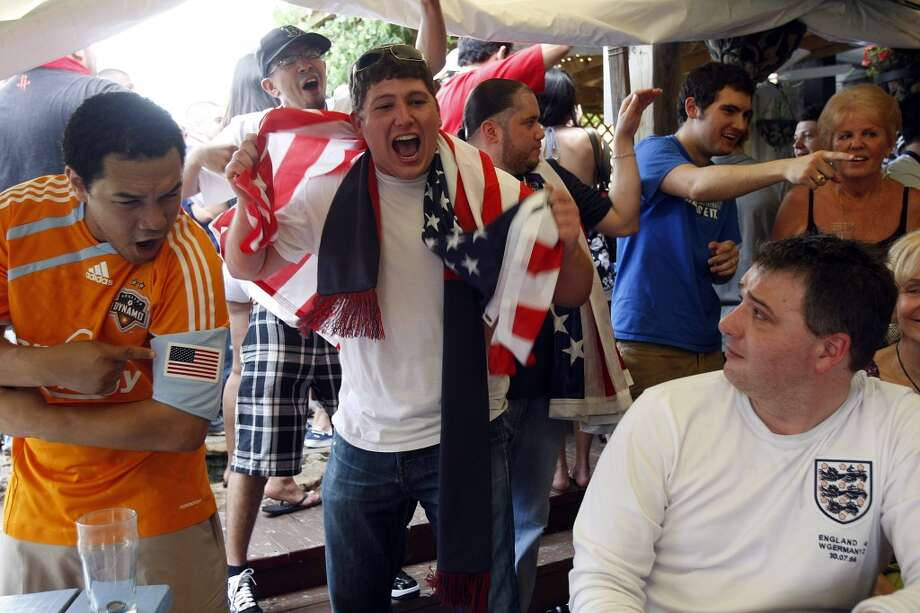 """Robert Ford (right) who is originally from London, England but now lives here in Houston, is heckled by U.S. soccer fans, Malik Smith (left) and Jason McClelland, as hundreds of U.S. and England fans gathered at Richmond Arms Pub to watch the U.S. and England played to a 1-1 tie in the World Cup Friday, June 11, 2010, in Houston.  When asked how important the game was for England, Ford said. """"It doesn't compare to my first born, but perhaps my second. I may be leaving the country this afternoon if we lose."""" ( Johnny Hanson / Chronicle ) Photo: Houston Chronicle"""