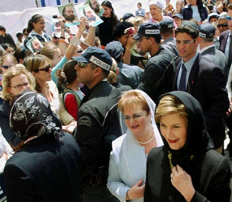 ** ALTERNATIVE CROP OF JRL816 ** U.S. first lady Laura Bush and Gila Katsav, the wife of Israeli President Moshe Katsav, walk past demonstrators demanding the release of convicted Israeli spy Jonathan Pollard as they arrive at the Western Wall in Jerusalem's Old City Sunday May 22, 2005.  Anti-U.S. protesters later heckled Laura Bush at the Al Aqsa Mosque compound, during a Mideast tour meant to defuse growing  anti-American sentiment in the region.(AP Photo/Ariel Jerosolimski) ** ISRAEL OUT ** Photo: AP