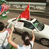 CONTACT FILED:  CHEN SHUI-BIAN 6/3/2001--Pro-Taiwanese separatist demonstrators heckle a passing car filled with opposing demonstrators supporting a cause for a unified China, today, in front of a restaurant along the Katy Freeway near the West Belt.  Taiwanese President Chen Shui-ben was meeting with U.S. Representative Tom DeLay and other members of Congress over lunch.  Photo by Steve Ueckert / Choronicle