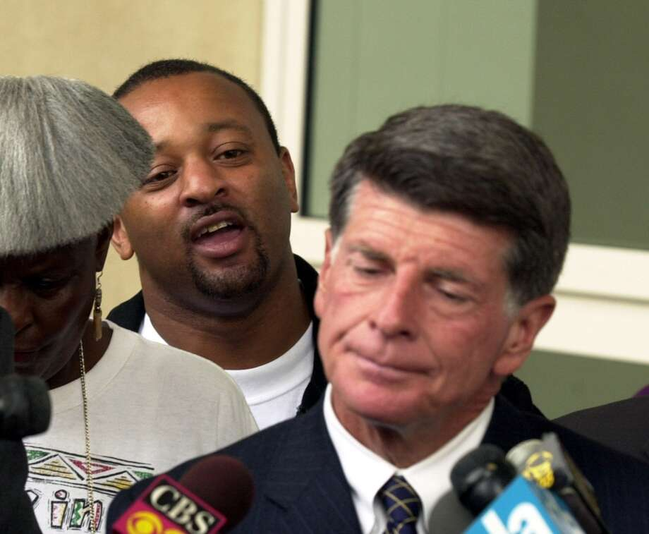 Activist Najee Ali, left back, heckles defense attorney John Burnett outside the the Airport Courthouse Thursday, Sept. 5, 2002, in Los Angeles. Inglewood Police officers Jeremy Morse, left, and Bijan Darvish appeared at a preliminary hearing Thursday on charges in connection with the videotaped arrest July 6 of a black teenager. Morse is charged with assault under the color of authority and Darvish is charged with filing a false police report. (AP Photo/Brad Graverson, Pool) Photo: AP