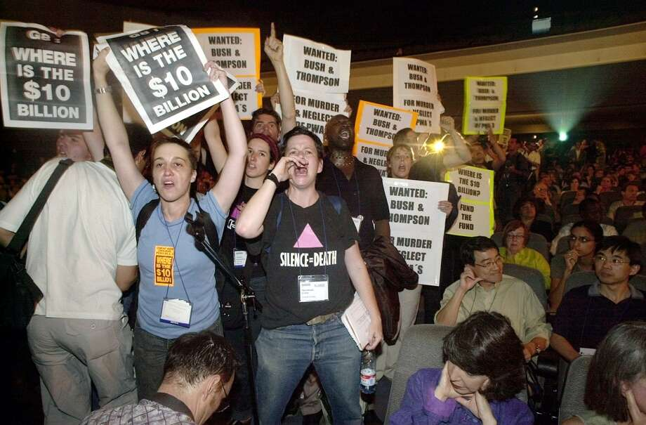 Members of the Act Up AIDS activist group heckle U.S. Secretary of Health and Human Services Tommy Thompson during his address to delegates at the International AIDS conference in Barcelona, Spain, Tuesday, July 9, 2002. The group was demanding more active U.S. government support in the fight against AIDS. (AP Photo/Denis Doyle)  HOUCHRON CAPTION  (07/10/2002):  Members of the Act Up AIDS activist group badger U.S. Secretary of Health and Human Services Tommy Thompson Tuesday in Barcelona, Sapin. Protesters demand more U.S. funding for the fight against AIDS. Photo: AP